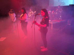 Grupo de música con luz rosa